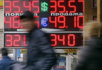 People pass by a board displaying exchange currency rates in Moscow