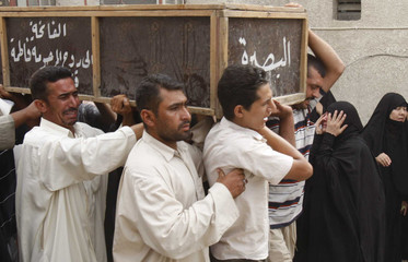 Residents carry a coffin of a victim who was killed in Monday's bomb attack during a funeral in Basra