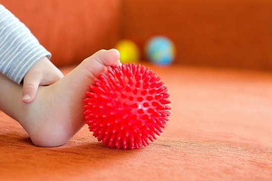 Toddler massaging with ball his foot. Exercise stimulates right development of foot.