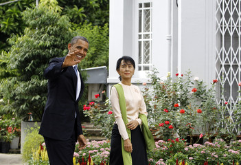 U.S. President Barack Obama and Myanmar's opposition leader Aung San Suu Kyi walk together during their meeting at her home in Yangon
