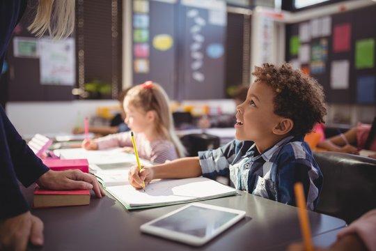 Teacher interacting with schoolboy in classroom