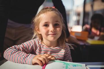 Portrait of cute schoolgirl sitting in classroom