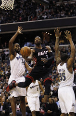 Miami Heat's Wade goes to hoop past Washington Wizards defenders during the second quarter of their NBA basketball game in Washington