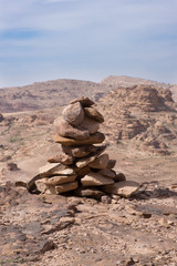 Close up of a cairn on the edge of a cliff near Petra Jordan. Rugged mountains and light blue cloudy sky are in the background.