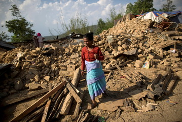 A woman walks through the rubble of collapsed houses at a village affected after an earthquake in Sindhupalchowk