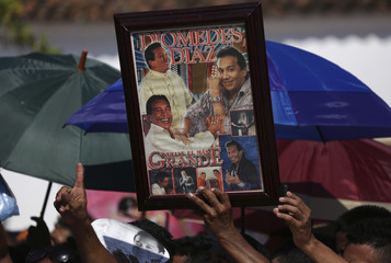 People hold posters and umbrellas as they gather to attend the funeral ceremony of  musician Diomedez Diaz at the main square of Valledupar