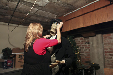 Hotel manager Robin Brekhus attaches the head to one of the many Halloween decorations while in the basement of the Gadsden Hotel in Douglas