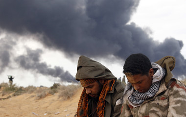 Rebel fighters pray in front of a burning gas storage terminal during a battle on the road between Ras Lanuf and Bin Jawad