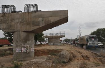 Vehicles travel past a Delhi-Jaipur national highway flyover under construction at Manesar