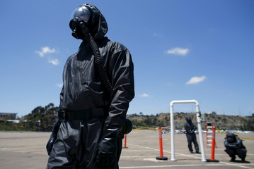 Emergency medical personnel wearing Level 2 hazmat suits wait to run a radiation check while training for a mass-casualty hazardous materials disaster in San Diego