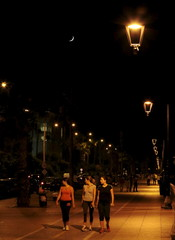 Women walk on a street by the the Corniche Beirut seaside promenade, as a crescent moon is seen in the night sky, on the second day of Ramadan in Beirut