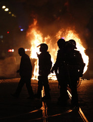 Policemen walk in front of burning barricades during clashes near the Parliament in Lisbon