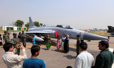 People take pictures with a JF-17 Thunder fighter jetf during a ceremony to commemorate Defence Day, or Pakistan's Memorial Day, at the Nur Khan air base in Islamabad