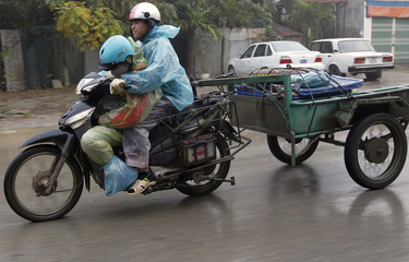 A carpenter rides a motorcycle with his wife as they return home from delivering products to dealers on a street in Hanoi