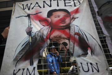 "A protester talks on his phone behind a burned banner depicting North Korea's leader Kim as a character from ""Journey to the West"" during an anti-North Korea rally in Seoul"