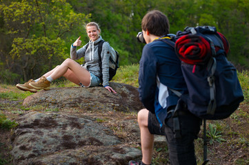 travel, hiking, backpacking, tourism and people concept. Smiling couple with backpacks taking picture by camera in nature