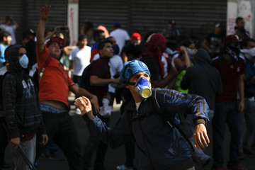 Opposition demonstrators throw stones at police during a protest against Venezuela's President Maduro's government in Caracas
