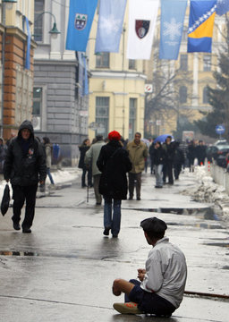 A handicapped Bosnian man begs for money as snow falls in the central street of Sarajevo