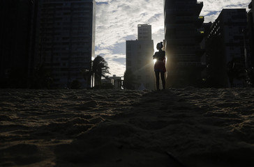 A woman listens to music as the sun sets as seen between buildings on Boa Viagem beach in Recife