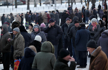 People wait for monthly humanitarian aid packages in front of the Donbass hockey stadium in Donetsk