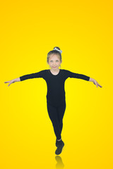 Smiling full lenght portrait of a little girl ballerina trying ballet position on yellow background