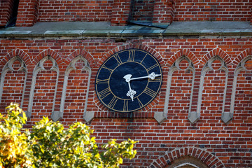 Church clock on red brick background.