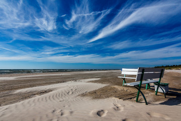 Bench on a white sand beach with blue dark blue sky.