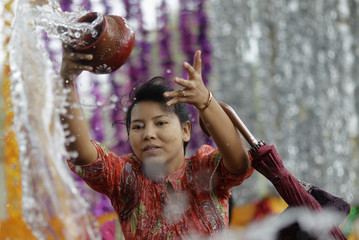 Devotee pours water on a Bodhi tree during Kason Watering Festival celebrations at the Shwedagon Pagoda in Yangon