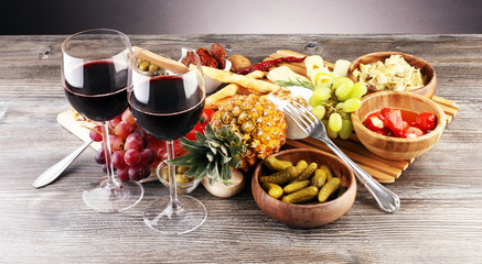 Italian antipasti wine snacks set. Cheese variety, Mediterranean olives, pickles, Prosciutto di Parma with grapes, wine in glasses over black grunge background