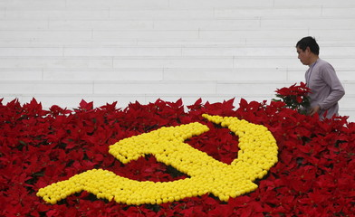 A man arranges flowers used to set up a decoration with the Communist logo promoting the upcoming 12th national congress of the Vietnam's Communist Party at the national convention center, the congress venue, in Hanoi