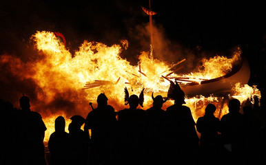 Flames engulf a viking longboat as it is set on fire during the Up Helly Aa fire festival in Lerwick