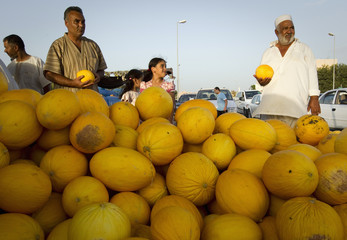 Shoppers buy melons at a fruit and vegetable market in Tripoli