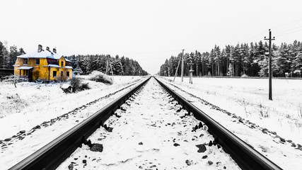 Isolated yellow house beside black and white railroad tracks.