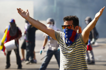 Anti-government protesters clash with police during a protest against Nicolas Maduro's government in Caracas