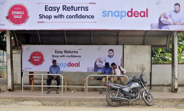 Commuters sit at a bus stop adorned with an advertisement of Indian online marketplace Snapdeal featuring Bollywood actor Aamir Khan, in Bengaluru, India