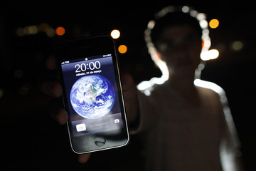 A man poses with an iPhone during Earth Hour in the center of Brasilia