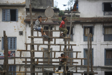 Children climbs a wooden frame build specially for the Indra Jatra festival to light lamps during the festival in Kathmandu