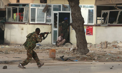 A Somali government soldier runs to take position during gunfire after a suicide bomb attack outside Nasahablood hotel in Somalia's capital Mogadishu