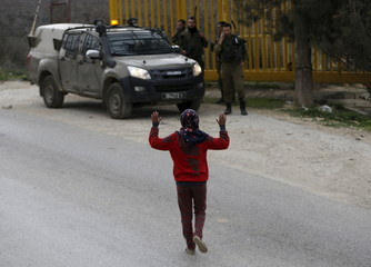 A Palestinian girl raises her arms up as she approaches Israeli soldiers to see her 14-year-old detained brother near Hebron
