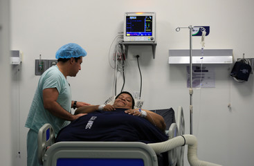 Oscar Vasquez Morales, 44, considered the most obese man in the country at about 400 kg, gestures next to bariatric surgeon in clinic in Cali, Colombia