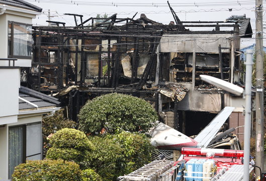 The tail section of a crashed light plane and burning house are seen after the plane went down in a residential area and burst into flames, in Chofu, outskirt of Tokyo