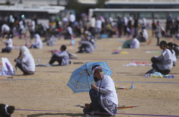 Palestinian schoolgirl holds an umbrella as others fly a kite to show solidarity with the Japanese people, near the Japan-funded housing project in Khan Younis in the southern Gaza Strip