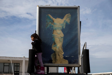 A girl stands on a disused airstair during a protest of refugees and migrants, most of them Afghans, at the premises of the refugee camp at the old Hellenikon airport in Athens