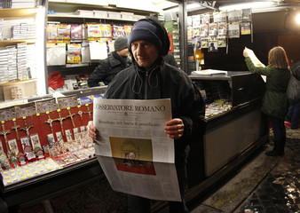 A man holds the Osservatore Romano newspaper in Rome