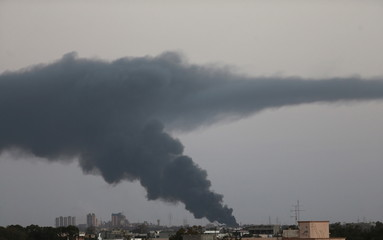 Black smoke billows in the sky above areas where clashes are taking place between pro-government forces, who are backed by the locals, and the Shura Council of Libyan Revolutionaries in Benghazi