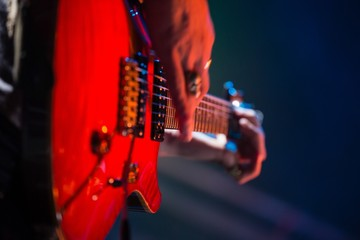 Close-up of guitarist playing guitar on stage