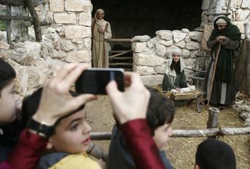 Israeli Arab pupils watch actors re-enact a Nativity scene in Nazareth