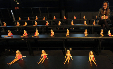 A woman smiles as she looks at Barbie dolls on the benches of the audience before CIA Maritima's Summer 2012 collection  during Sao Paulo Fashion week