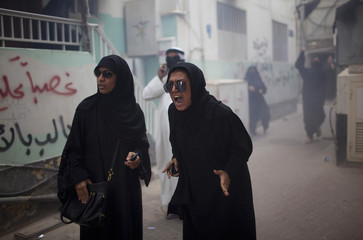 Protesters chant slogans after police used a flashbang stun grenade during an anti-government rally in Manama