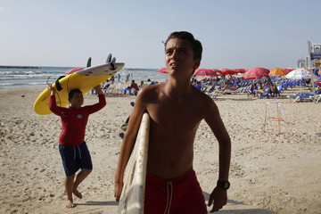 Boys carry their surf boards ashore after their lesson was cancelled following a mid-air explosion from a rocket which was intercepted by the Iron Dome defense system, in Tel Aviv